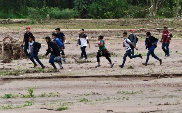 Migrantes rumbo a la frontera con Guatemala rumbo a Estados Unidos, cruzan el cauce seco del río Copán en el municipio de Santa Rita, en el departamento hondureño de Copán, el 15 de enero de 2021. (Foto de Orlando Sierra / AFP vía Getty Images)