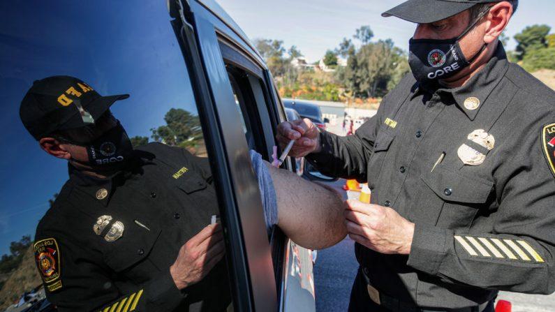 El asistente de bomberos de Los Ángeles, Ellsworth Fortman (der.), administra una vacuna Covid-19 cuando comienza la vacunación masiva de los trabajadores de la salud en el Dodger Stadium, el 15 de enero de 2021, en Los Ángeles, California. (IRFAN KHAN/POOL/AFP a través de Getty Images)