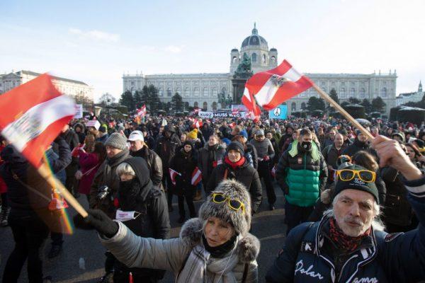 Los manifestantes ondean la bandera austríaca durante una protesta contra las restricciones por el covid-19 y sostienen una pancarta de 'Kurz debe ir' en Maria Theresien Platz en Viena, Austria, el 16 de enero de 2021. (Foto de Alex Halada / AFP a través de Getty Images)