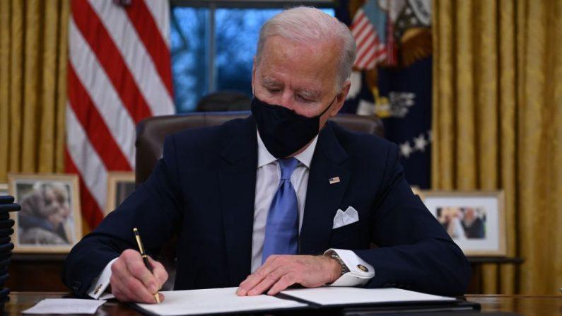 El presidente de EE.UU., Joe Biden, firma en el Despacho Oval de la Casa Blanca, en Washington D.C., una serie de órdenes ejecutivas tras jurar por su mandato en el Capitolio de EE.UU. el 20 de enero de 2021.(Jim Watson/AFP vía Getty Images)