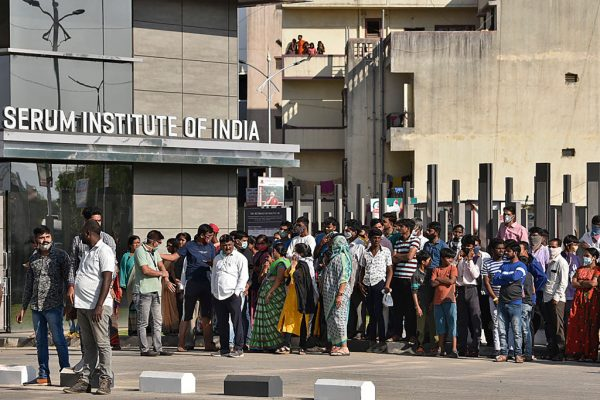 La gente se para frente al Instituto del Suero de la India después de que estalló un incendio, en Pune el 21 de enero de 2021. (Foto de AFP via Getty Images)