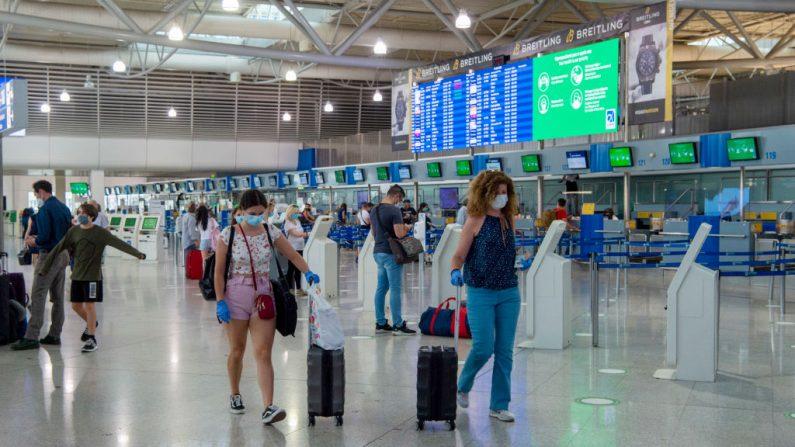 Los pasajeros usan mascarillas y guantes protectores cuando llegan al Aeropuerto Internacional Eleftherios Venizelos en Atenas el 15 de junio de 2020 en Atenas, Grecia. (Foto de Milos Bicanski / Getty Images)