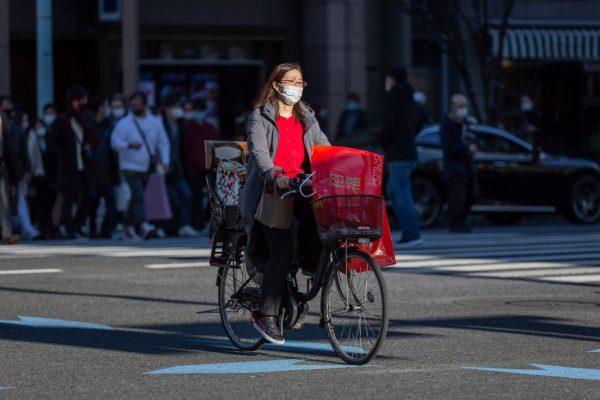 Una mujer con una mascarilla monta en bicicleta en la zona comercial de Ginza el 2 de enero de 2021 en Tokio, Japón. (Foto de Yuichi Yamazaki / Getty Images)