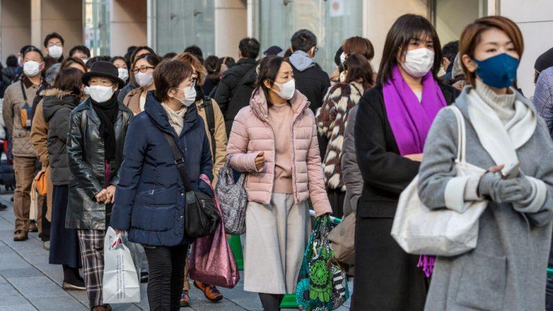 Personas con mascarillas esperan en una fila para la puerta de los grandes almacenes Matsuya Ginza el 02 de enero de 2021 en Tokio, Japón. (Foto de Yuichi Yamazaki / Getty Images)