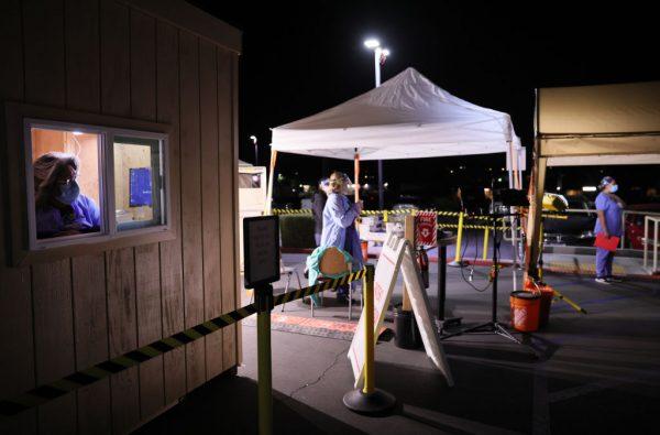 Trabajadores esperan en carpas de clasificación y un puesto de información para pacientes instalado en el estacionamiento del Providence St. Mary Medical Center en medio de un aumento de pacientes con COVID-19 en el sur de California el 5 de enero de 2021 en Apple Valley , California, EE.UU. (Foto de Mario Tama / Getty Images)
