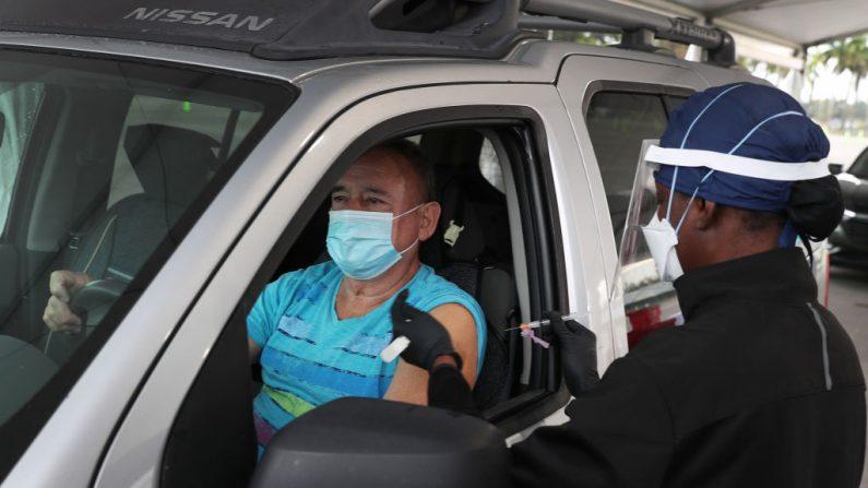 Armando Bravo recibe una vacuna COVID-19 de un trabajador de la salud en un sitio de drive-thru en Tropical Park, el 13 de enero de 2021, en Miami, Florida. (Joe Raedle/Getty Images)