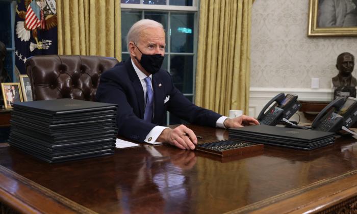 El presidente de Estados Unidos, Joe Biden, se prepara para firmar una serie de órdenes ejecutivas en el Escritorio Resolutivo del Despacho Oval apenas horas después de su toma de posesión el 20 de enero de 2021 en Washington. (Chip Somodevilla/Getty Images)