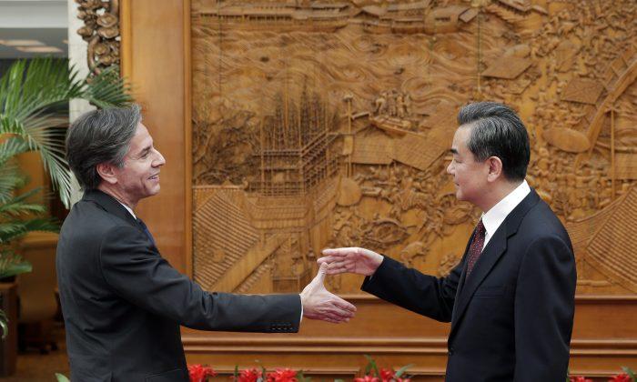 El subsecretario de Estado de Estados Unidos, Antony Blinken, le da la mano al ministro de Relaciones Exteriores de China, Wang Yi, en el Salón de los olivos  antes de una reunión en la oficina del Ministerio de Relaciones Exteriores, en Beijing, el 11 de febrero de 2015. (Andy Wong - Pool/Getty Images)