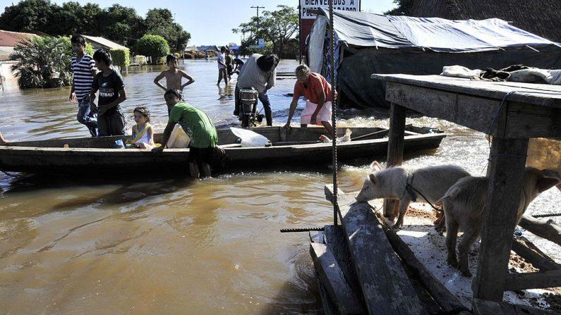 Una familia intenta recuperar sus pertenencias personales con una embarcación en un área inundada por el río Mamore durante las fuertes lluvias en Trinidad, Bolivia, el 17 de febrero de 2014. (Foto de Aizar Raldes / AFP a través de Getty Images)