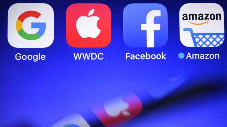 Esta fotografía tomada el 28 de septiembre de 2017, muestra un teléfono inteligente siendo operado frente a los logotipos de GAFA (acrónimo de los gigantes de la web Google, Apple, Facebook y Amazon) como fondo en Hédé-Bazouges, oeste de Francia. (DAMIEN MEYER/AFP vía Getty Images)