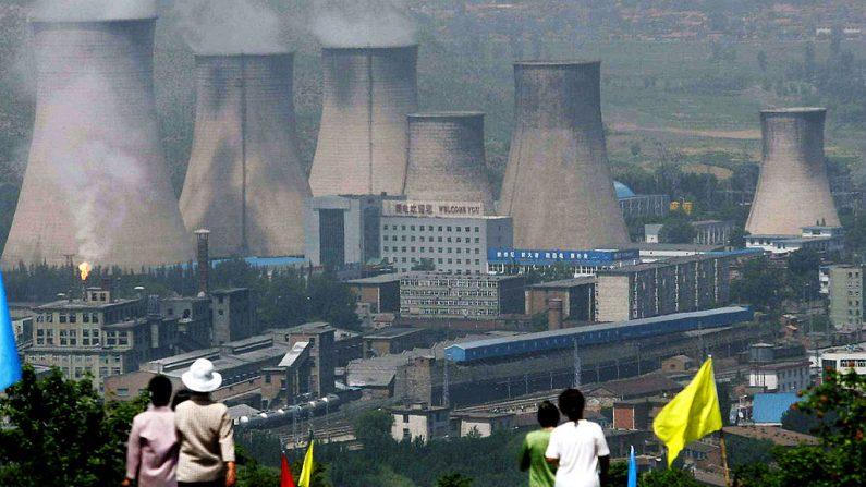 Los residentes caminan por una carretera que conduce a la central eléctrica del condado en Zhangjiakou, provincia de Hebei, en el noreste de China, el 19 de junio de 2005. (Foto de STR / AFP a través de Getty Images)