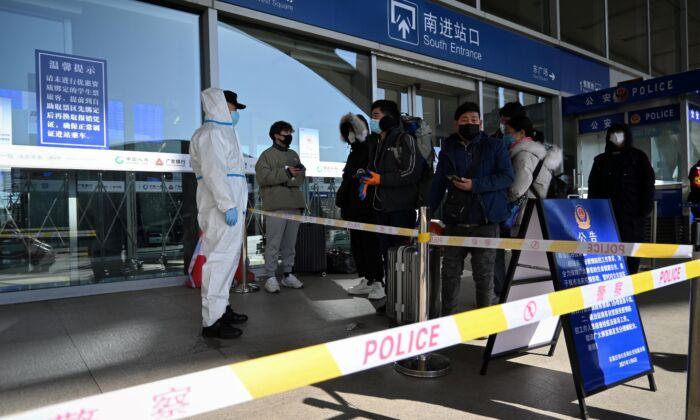 Pasajeros siendo detenidos a la entrada de una estación de ferrocarril mientras la ciudad corta los enlaces de transporte y prohíbe a los residentes salir, después del gran brote de COVID-19 en Shijiazhuang, en la provincia de Hebei, en el norte de China, el 7 de enero de 2021. (STR/CNS/AFP vía Getty Images)