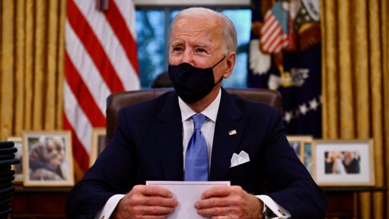 El presidente Joe Biden se prepara para firmar una serie de órdenes en la Oficina Oval de la Casa Blanca en Washington, el 20 de enero de 2021. (Jim Watson/AFP a través de Getty Images)