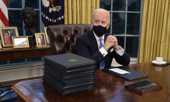 El presidente Joe Biden se prepara para firmar una serie de órdenes ejecutivas, en el Escritorio del Despacho Oval, horas después de su toma de posesión, en Washington, el 20 de enero de 2021. (Chip Somodevilla/Getty Images)