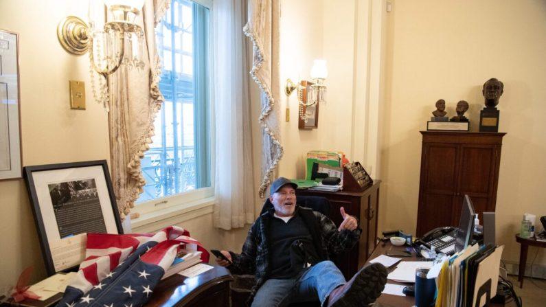 Richard Barnett, un manifestante, se sienta dentro de la oficina de la presidenta de la Cámara de Representantes de Estados Unidos, Nancy Pelosi, dentro del Capitolio en Washington, el 6 de enero de 2021. (Saul Loeb/AFP a través de Getty Images)