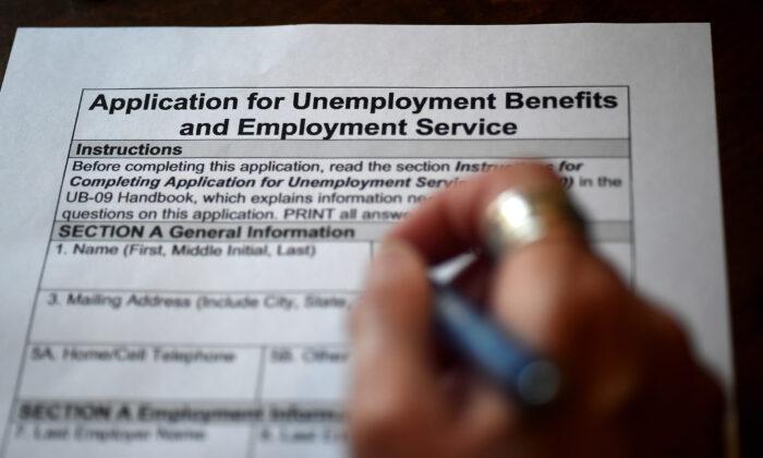 En esta ilustración fotográfica, una persona presenta una solicitud de beneficios por desempleo en Arlington, Virginia (EE.UU.), el 16 de abril de 2020. (Olivier Douliery/AFP vía Getty Images)