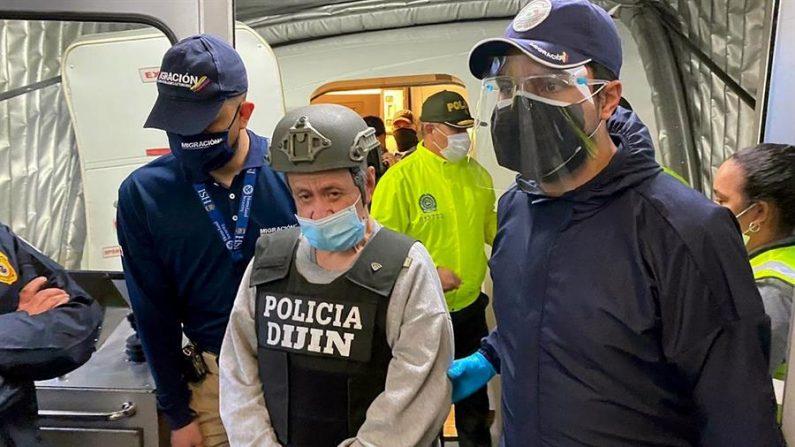 Fotografía cedida por Migración Colombia que muestra al exjefe paramilitar colombiano Hernán Giraldo Serna (c), luego de su llegada en calidad de deportado desde los Estados Unidos el 25 de enero de 2021, a Bogotá (Colombia). EFE/ Migración Colombia