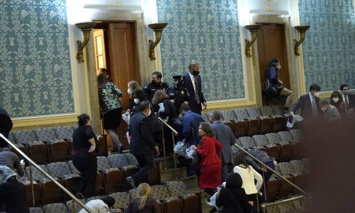 Los miembros del Congreso evacuan la Cámara mientras los manifestantes intentan ingresar durante una sesión conjunta del Congreso en Washington el 6 de enero de 2021. (Drew Angerer/Getty Images)