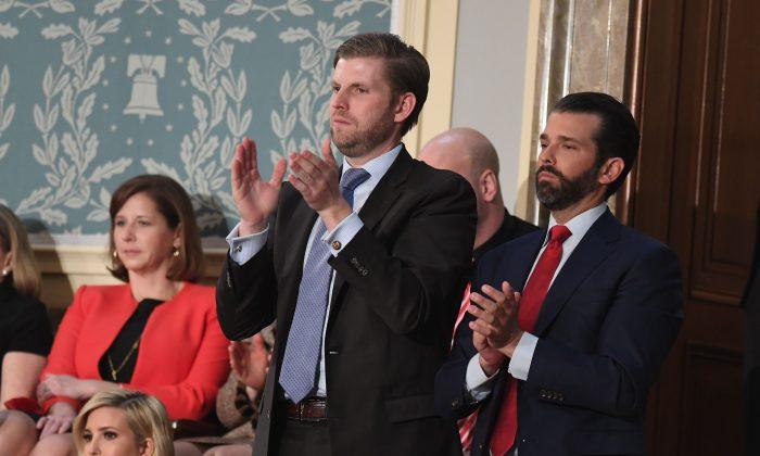 Eric Trump (Izq.) y Donald Trump Jr. aplauden mientras su padre, el presidente Donald Trump, pronuncia el discurso sobre el Estado de la Unión ante una Sesión Conjunta del Congreso el 5 de febrero de 2019. (SAUL LOEB/AFP/Getty Images)