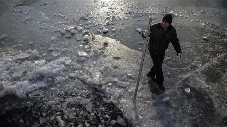 Un ciudadano quita un bloque de hielo antes de nadar, en un frío día de invierno en la ciudad de Beijing, China, el 7 de enero de 2021. (EFE/EPA/WU HONG).