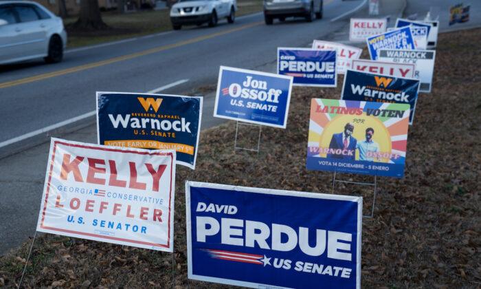 Las señales se alinean en una carretera en un lugar de votación del condado de Gwinnett el 5 de enero de 2021 en Atlanta, Georgia. Las urnas se abrieron en toda Georgia en las dos elecciones de desempate, enfrentando a los titulares del cargo, el senador David Perdue (R-GA) y la senadora Kelly Loeffler (R-GA) contra los candidatos demócratas, el reverendo Raphael Warnock y Jon Ossoff. (Megan Varner/Getty Images)