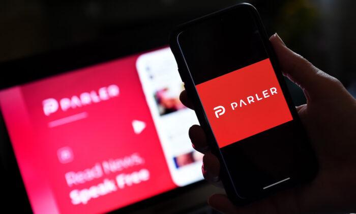 El logo de la red social Parler en un smartphone con su página web al fondo. (Olivier Douliery/Archivo/AFP vía Getty Images)
