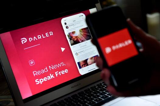 El logotipo de Parler, en un teléfono inteligente, junto a su sitio web de fondo, en Arlington, Virginia, el 2 de julio de 2020. (Olivier Douliery/AFP a través de Getty Images)
