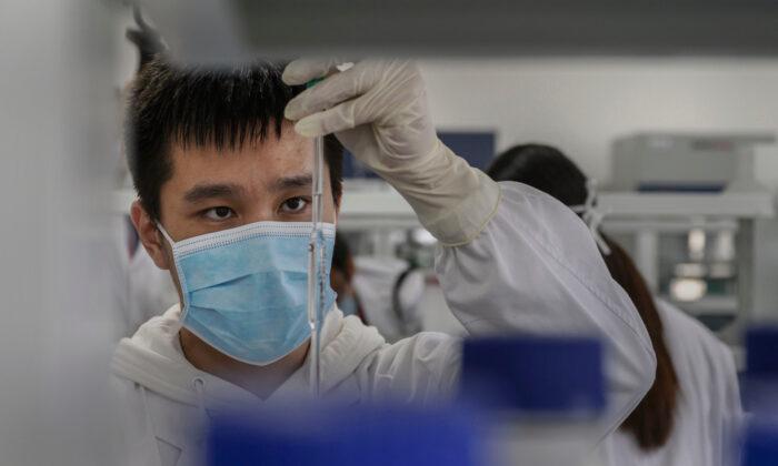 Un técnico trabaja en un laboratorio en Sinovac Biotech, donde la compañía está produciendo su posible vacuna COVID-19 CoronaVac durante un viaje de medios en Beijing, China, el 24 de septiembre de 2020. (Kevin Frayer/Getty Images)