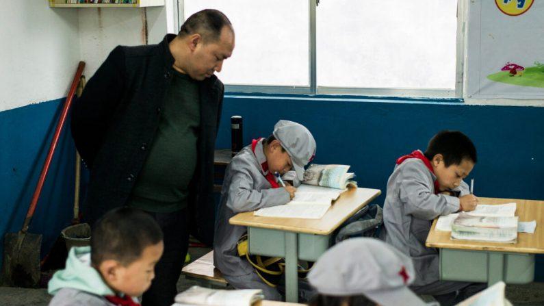 """Un maestro que supervisa a estudiantes en la escuela primaria Yang Dezhi """"Ejército Rojo"""" en Wenshui, de Xishui, en la provincia de Guizhou, China, el 7 de noviembre de 2016. (FRED DUFOUR / AFP a través de Getty Images)"""