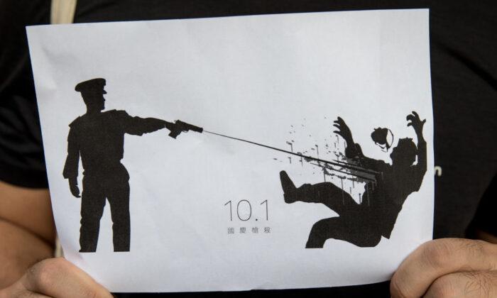 Un hombre sostiene un cartel que representa el disparo de un policía contra un manifestante durante las protestas del 1 de octubre de 2019 en Hong Kong, China, el 2 de octubre de 2019. (Chris McGrath/Getty Images)