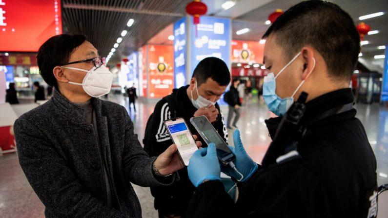 Un pasajero muestra un código QR verde en su teléfono para mostrar su estado de salud a la seguridad al llegar a la estación de tren de Wenzhou, en Wenzhou, China, el 28 de febrero de 2020. (Noel Celis/AFP vía Getty Images)