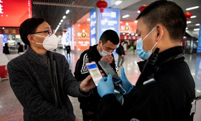Un pasajero muestra un código QR verde para dar a conocer su estado de salud al personal de seguridad al llegar a la estación de tren de Wenzhou, en Wenzhou, China, el 28 de febrero de 2020. (Noel Celis/AFP a través de Getty Images)