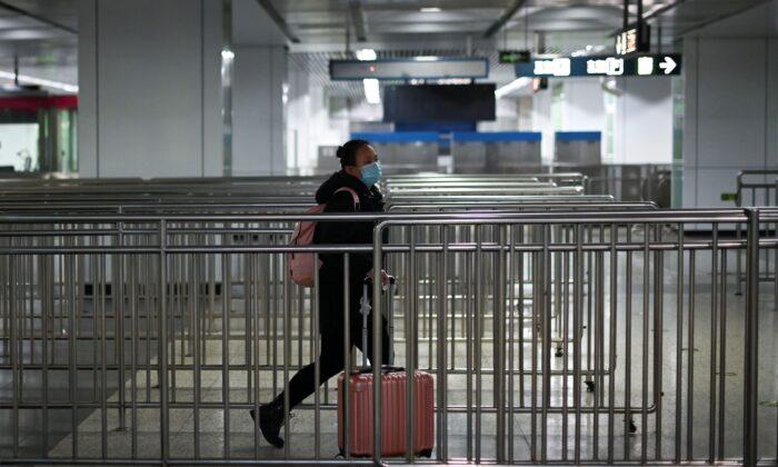 Una mujer con una máscara camina en una estación de metro en Beijing, el 28 de marzo de 2020. (Wang Zhao/AFP a través de Getty Images)