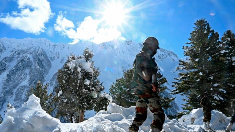 Un soldado del ejército indio se para en una carretera cubierta de nieve después de nevadas cerca del paso de montaña Zojila que conecta Srinagar con el territorio de la unión de Ladakh, en la frontera con China el 26 de noviembre de 2020. (Foto de Tauseef Mustafa / AFP vía Getty Imágenes)