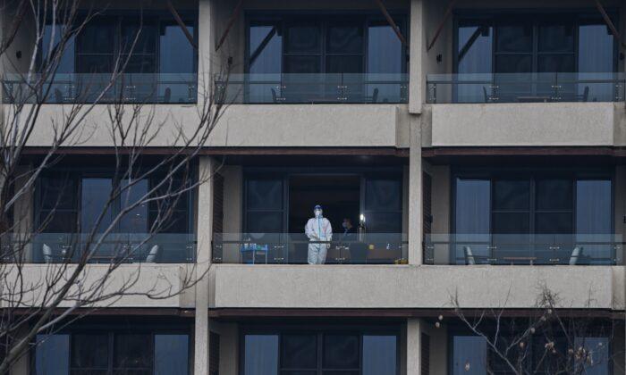 Un trabajador sanitario espera a los miembros del equipo de la Organización Mundial de la Salud (OMS) que investigan los orígenes del COVID-19 en un balcón del hotel Wuhan Hilton Optics Valley en Wuhan, China, el 6 de febrero de 2021. (HECTOR RETAMAL/AFP vía Getty Images)