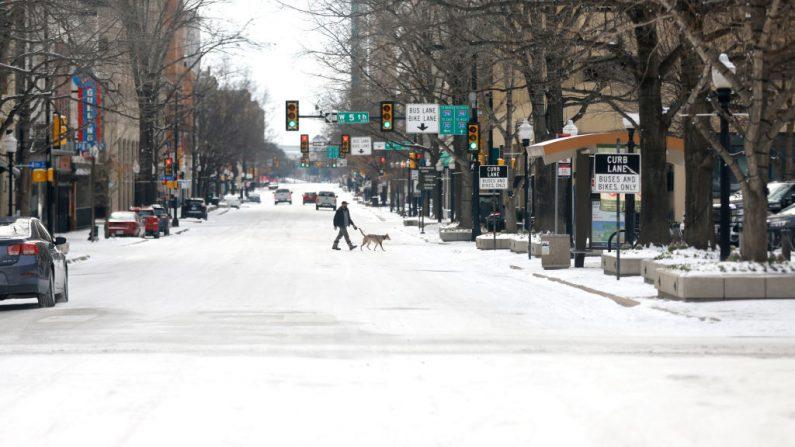 Un hombre pasea a su perro en el centro después de una tormenta de nieve el 16 de febrero de 2021 en Fort Worth, Texas (EE.UU.). (Ron Jenkins / Getty Images)