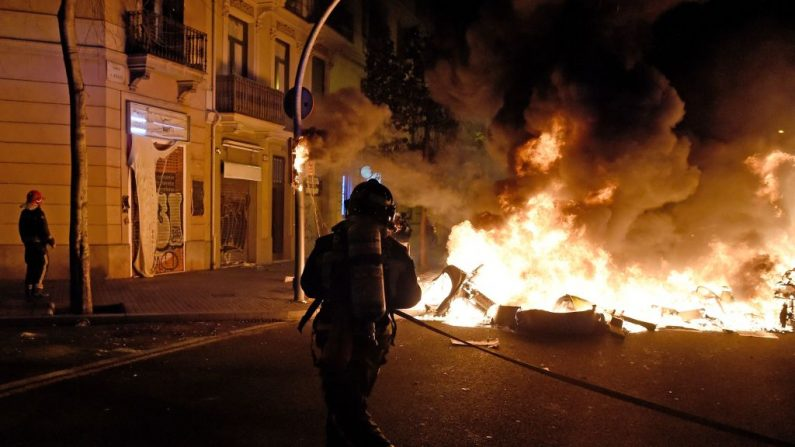 Los bomberos proceden a apagar las llamas tras los enfrentamientos entre manifestantes y policías durante la protesta contra el encarcelamiento del rapero español Pablo Hasel en Barcelona, España, el 18 de febrero de 2021. (Foto de Josep Lago / AFP vía Getty Images)