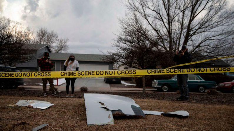Los residentes toman fotos de los escombros caídos del motor de un avión de United Airlines en el barrio de Broomfield, en las afueras de Denver, Colorado, el 20 de febrero de 2021. Un vuelo de United sufrió un fallo de motor el 20 de febrero, poco después de despegar de Denver en su camino a Hawái, dejando caer enormes escombros en una zona residencial antes de un aterrizaje de emergencia seguro, dijeron las autoridades. (Foto de Chet Strange / AFP vía Getty Images)