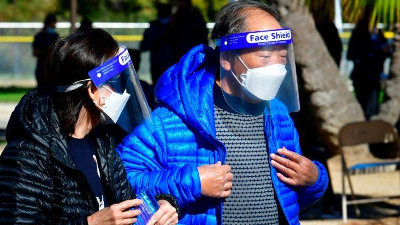 La gente usa protectores faciales y mascarillas en un sitio de vacunación contra la covid-19 en Los Ángeles, California el 23 de febrero de 2021. (Frederic J. Brown / AFP a través de Getty Images)