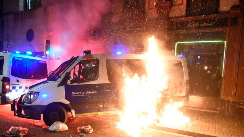 """Un cóctel Molotov estalla en llamas junto a un vehículo de la Policía Municipal durante una manifestación por diversos temas sociales bajo el lema """"Lucha, Crea Poder Popular"""" en Barcelona, España, el 27 de febrero de 2021. (Josep Lago / AFP a través de Getty Images)"""