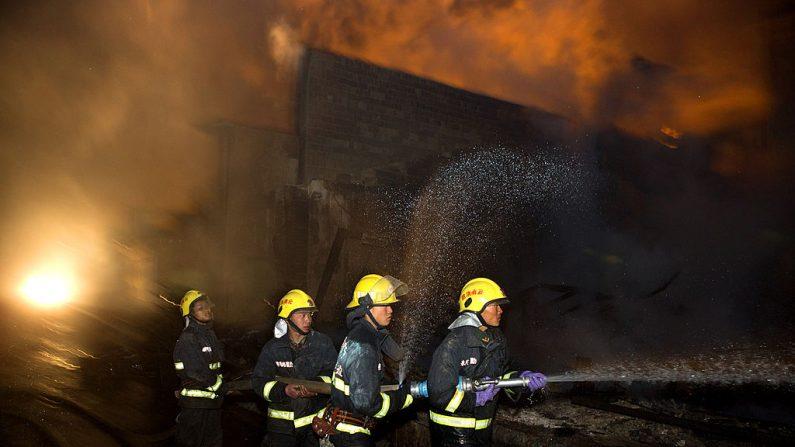 Los bomberos apagan un incendio en la antigua aldea tibetana de Dukezong en el condado de Shangri-La, provincia de Yunnan, suroeste de China, el 11 de enero de 2014. Imagen de archivo. (STR / AFP a través de Getty Images)