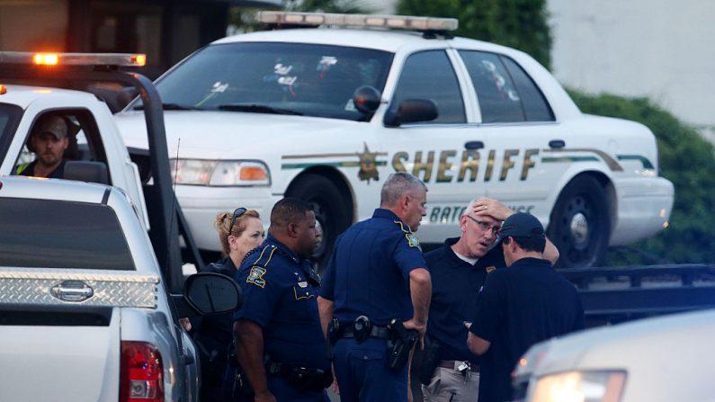 En la imagen, los agentes de policía se paran frente a un coche de policía de East Baton Rouge con agujeros de bala el 17 de julio de 2016 en Baton Rouge, Louisiana (EE.UU.). (Foto de Sean Gardner / Getty Images)