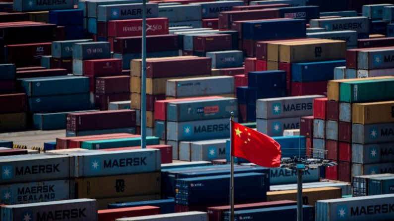 Una bandera china se ve frente a contenedores en el puerto de aguas profundas de Yangshan, un muelle de carga automatizado, en Shanghai, China, el 9 de abril de 2018. (Johannes Eisele / AFP a través de Getty Images)