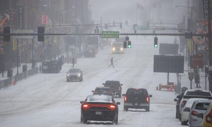 Vista general de Lower Broadway mientras vehículos y personas atraviesan la nieve y el hielo en Nashville, Tennessee, el 15 de febrero de 2021. (Brett Carlsen/Getty Images)