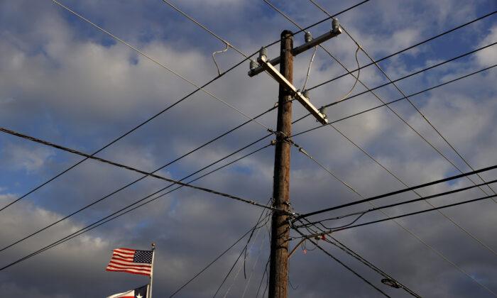Las banderas de EE.UU. y Texas ondean junto a un poste de electricidad en Houston, Texas, el 21 de febrero de 2021. (Justin Sullivan/Getty Images)