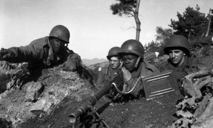 El Mayor Cleveland de la 2ª División de Inf. señala la posición norcoreana dirigida por los comunistas a su equipo de ametralladoras el 20 de noviembre de 1950, durante la Guerra de Corea. (Archivos Nacionales y Administración de Registros de EE.UU.)