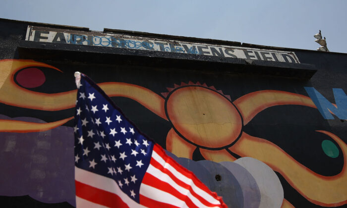 Una bandera estadounidense ondea en un automóvil junto a un mural en Maywood Park en Maywood, California, el 23 de junio de 2010. (David McNew / Getty Images)