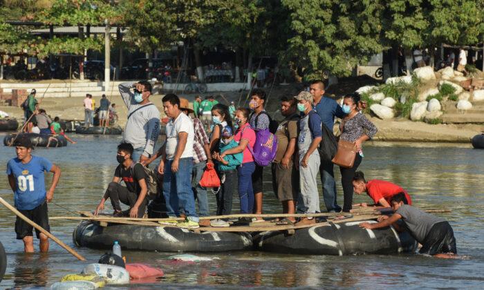 Viajeros cruzan el río Suchiate en una balsa desde Guatemala hasta Ciudad Hidalgo, México, el 18 de enero de 2021. Se espera la llegada de una nueva caravana de inmigrantes, en su mayoría de hondureños que se dirigen a Estados Unidos. (Isaac Guzman/AFP vía Getty Images)