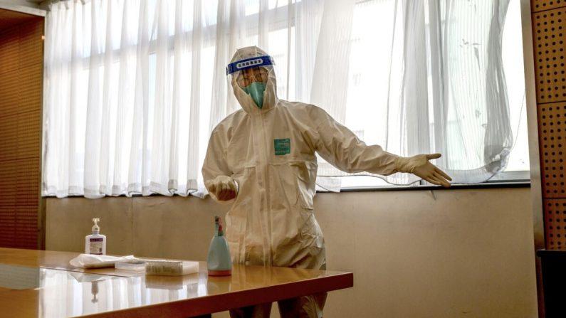 Un trabajador sanitario lleva un traje de protección mientras hace un gesto a un hombre para que se siente en un hotel de Beijing, China, antes de una prueba de ácido nucleico COVID-19 el 22 de octubre de 2020. (Kevin Frayer/Getty Images)