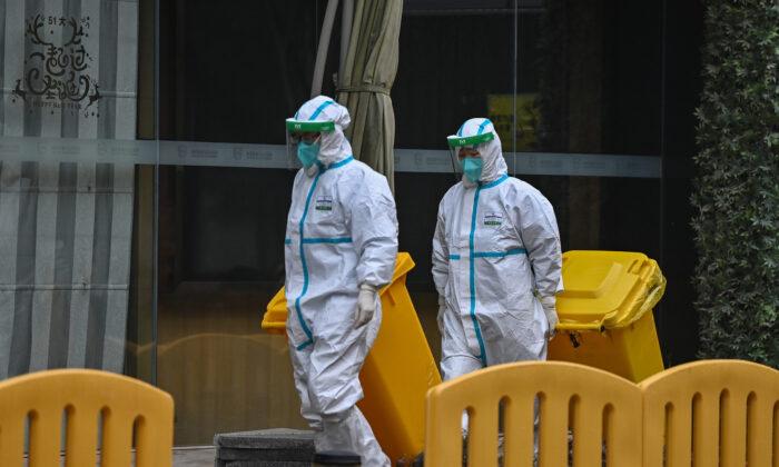Se observa a trabajadores con equipo de protección en los recintos de The Jade Boutique Hotel, donde los miembros del equipo de la Organización Mundial de la Salud (OMS) que investigan los orígenes de la pandemia por coronavirus Covid-19 deben completar su cuarentena, en Wuhan, provincia central de Hubei en China. el 28 de enero de 2021. (Hector Retamal/AFP a través de Getty Images)